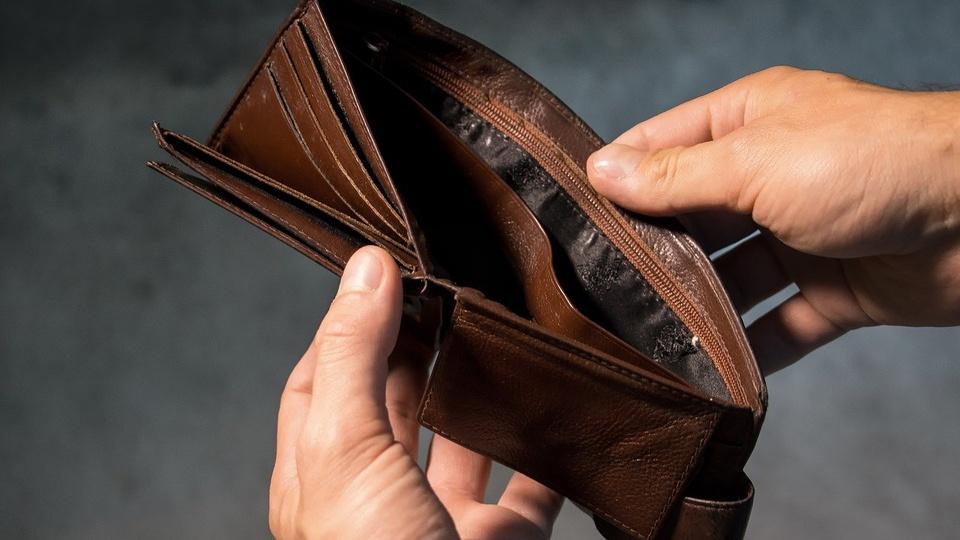 Como a recessão pode afetar sua vida, plano fechado nas mãos de uma pessoa abrindo uma carteira, a qual está carteira vazia