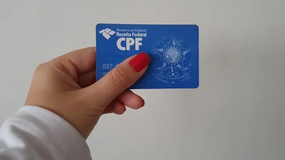 Como regularizar o CPF para receber o auxílio emergencial 2021: mão segurando cartão do CPF (Cadastro de Pessoa Física)