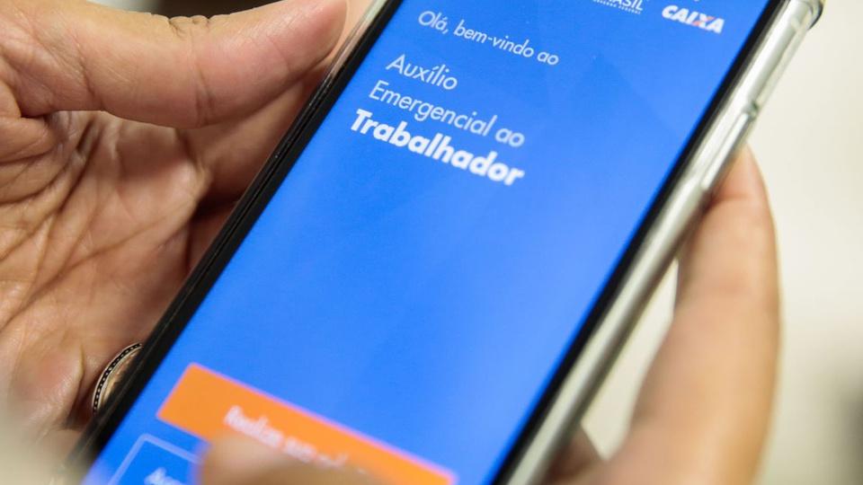 devolver auxílio emergencial: mão mexendo em celular. Na tela do aparelho, é possível ver a página do auxílio emergencial
