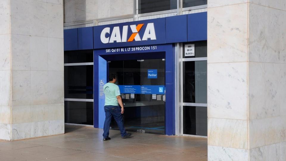Como sacar em dinheiro R$ 600 do auxílio emergencial: homem entrando em agência da Caixa