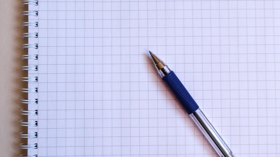 Concurso AGERGS: a imagem mostra  caneta sobre caderno de papel quadriculado