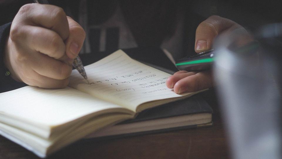 Concurso Água Clara - MS: pessoa com celular na mão e caneta em outra, escreve em caderno.