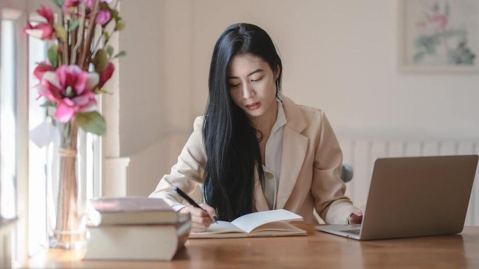 concurso alesc: imagem mostra mulher sentada em escrivaninha com computador aberto