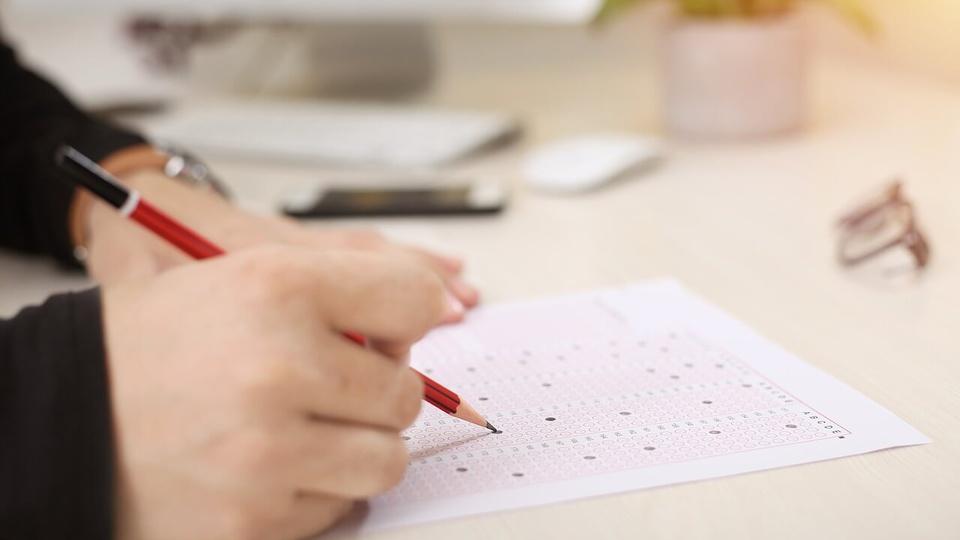 Concurso Barra do Corda: pessoa preenchendo um gabarito de prova, foto apenas mostra as mãos sobre a mesa, o lápis em punho, o gabarito, óculos, celular e outros objetivos no fundo