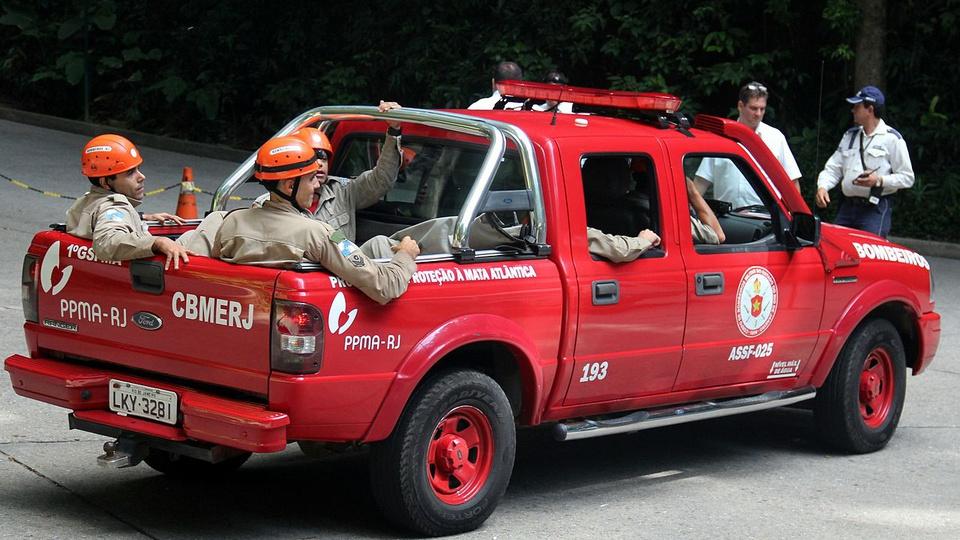 Concurso Bombeiros RJ: bombeiros dentro da carroceria de uma camionete vermelha do corpo de bombeiros