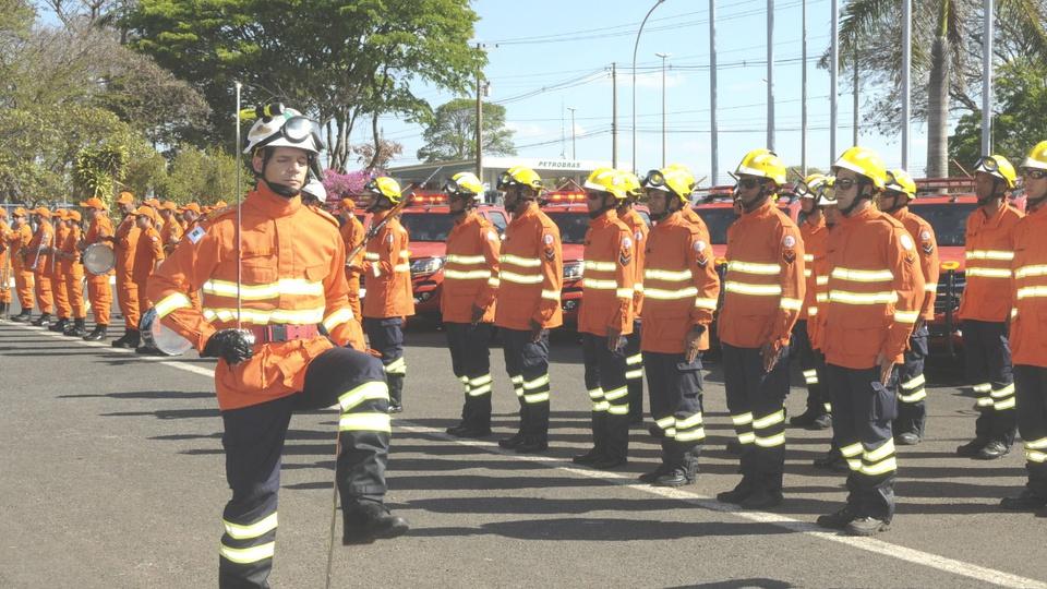 Concurso Bombeiros RJ é autorizado: bombeiros em solenidade. Todos estão com roupas apropriadas para conter incêndios