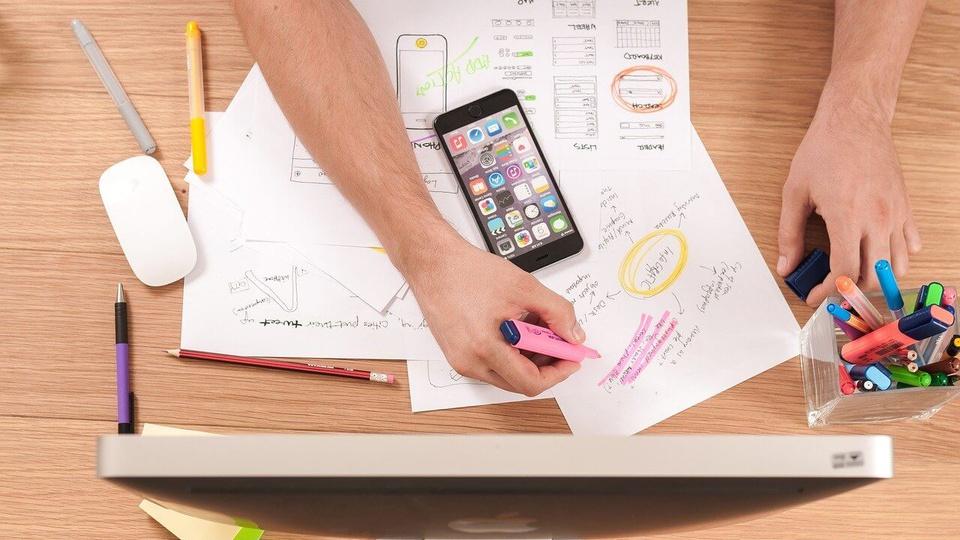 Concurso Câmara de Campo do Brito - SE: a foto mostra uma mesa com objetos de estudo, um braço masculino, canetas, papéis, monitor de computador, anotações,  celular, mouse,
