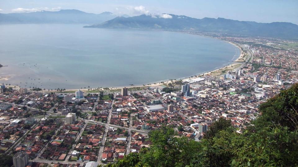 Concurso Câmara de Caraguatatuba SP: a foto mostra uma vista de Caraguatatuba sobre o morro santo antonio, prédios, floresta, casas, a praia