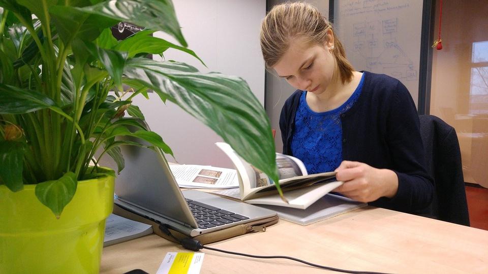 Concurso Câmara de Carneirinho - MG: edital publicado - mulher branca de cabelos loiros sentada a mesa escrevendo em um caderno