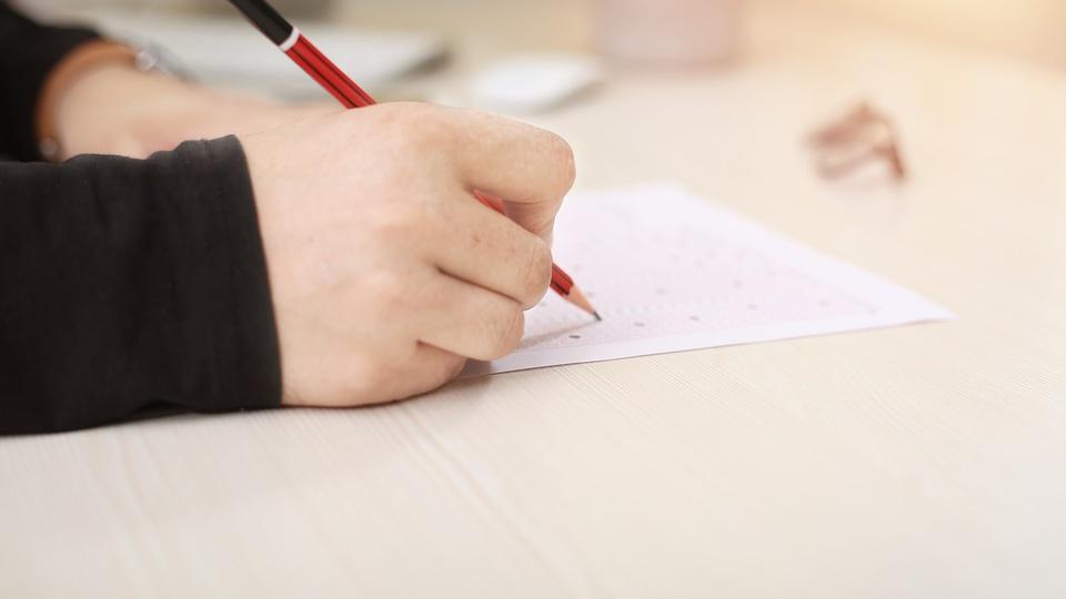 Concurso Câmara de Cerro Corá - RN, plano fechado em mão de pessoa escrevendo