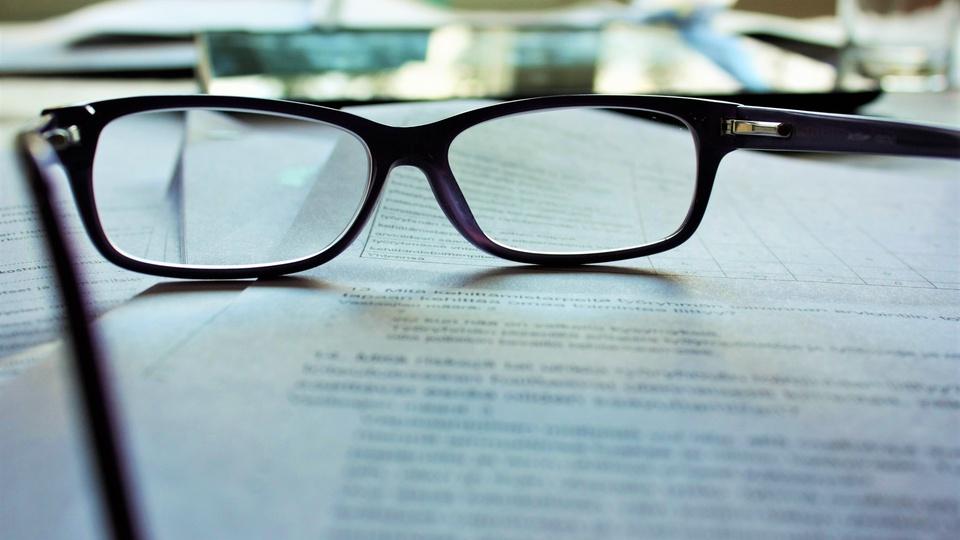 Concurso Câmara de Ibituruna - MG - imagem de um livro aberto com um óculos em cima