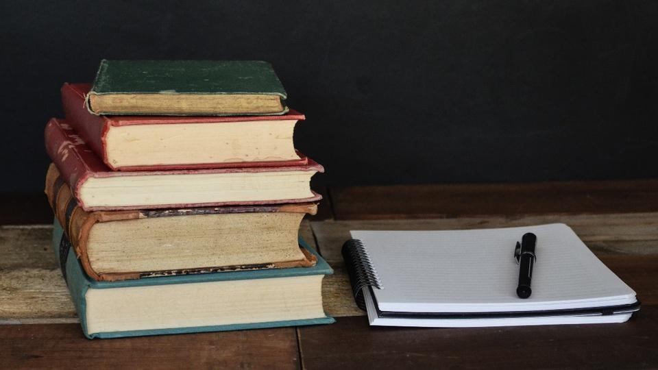 Concurso Câmara de Jaicós - PI: #PraCegoVer do lado esquerdo, estão dispostos livros antigos em tamanhos e cores variadas. Do lado direito, consta um caderno de arame com uma caneta por cima dele