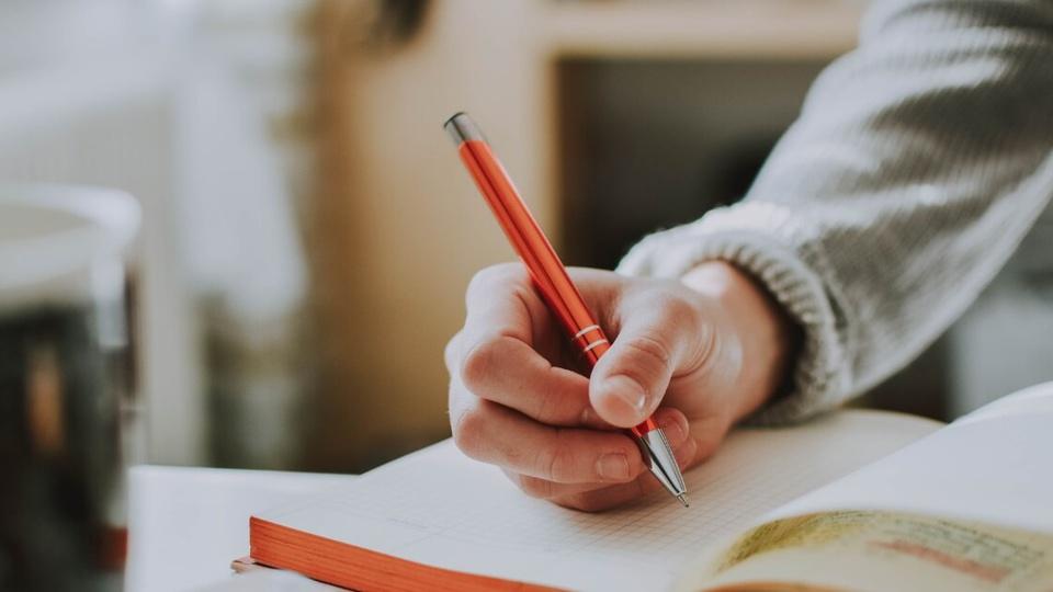 Concurso Câmara de Nova Esperança do Sudoeste - PR: destaque para o momento em que uma pessoa escreve em um caderno. A caneta metálica tem tom avermelhado