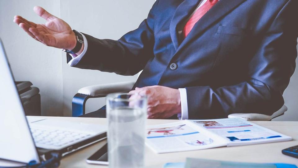 Concurso Câmara de Santa Amélia: a foto mostra homem com terno e gravata sentado diante de uma mesa com copo, papéis e outros objetos