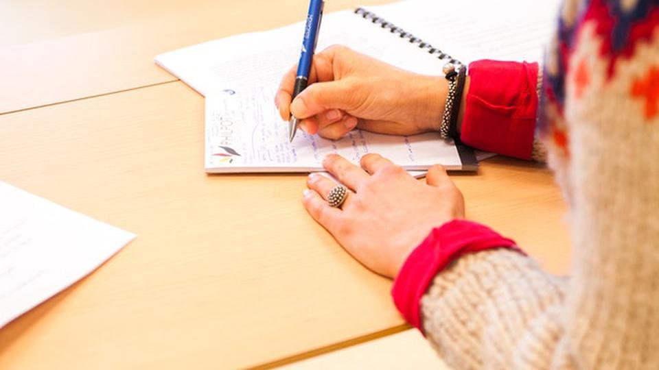 Concurso Câmara de São Felipe d'Oeste: aluna está anotando algo durante uma aula