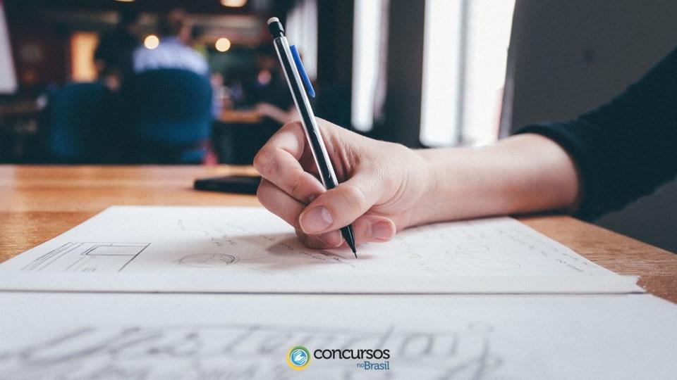 Concurso Câmara de São Gonçalo: a foto mostra uma pessoa segurando uma caneta e escrevendo em um papel