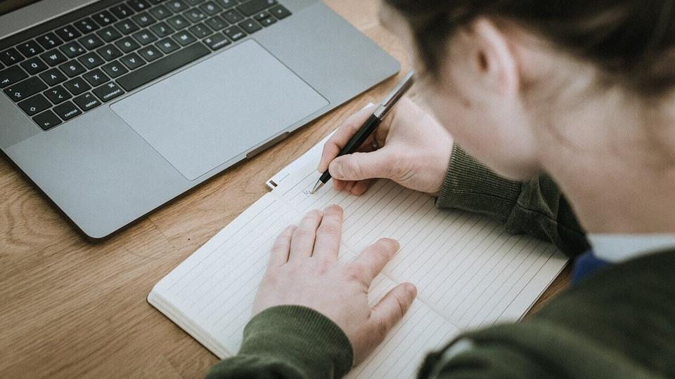 Concurso Câmara de Selvíria: pessoa escrevendo algo em caderno em frente a computador