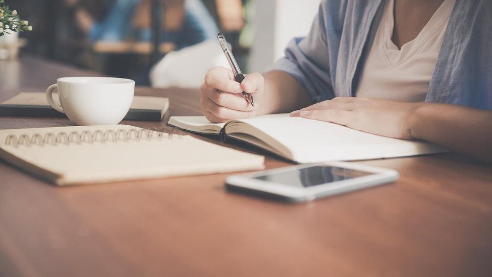 Concurso Câmara de Teresina - PI: cadernos, celular e xícara em cima de mesa e pessoa escrevendo em um dos cadernos
