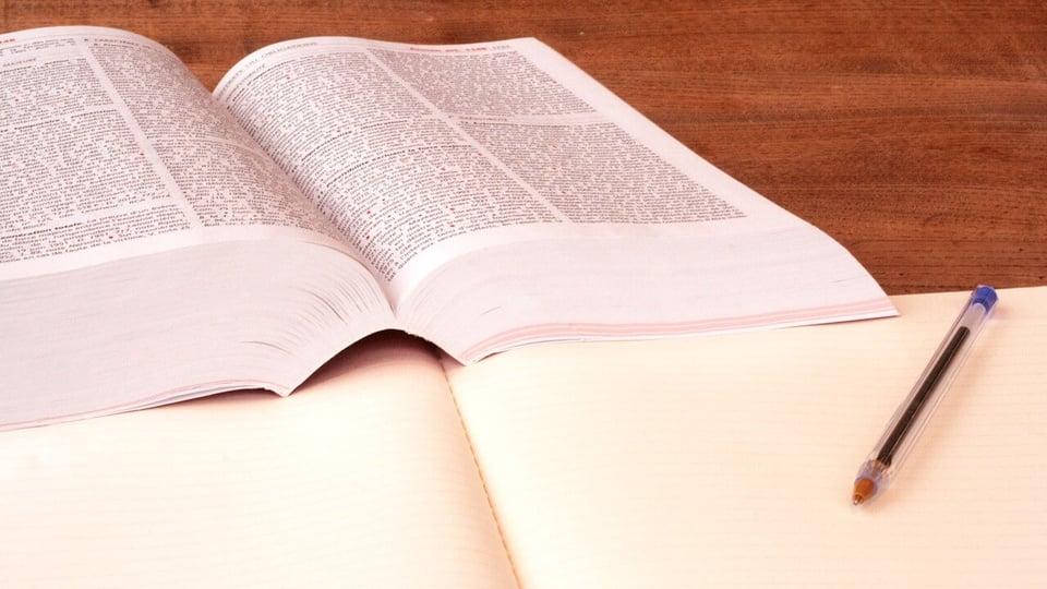 Concurso Câmara de Três Rios: imagem de um livro de direito, caneta e caderno sobre uma mesa
