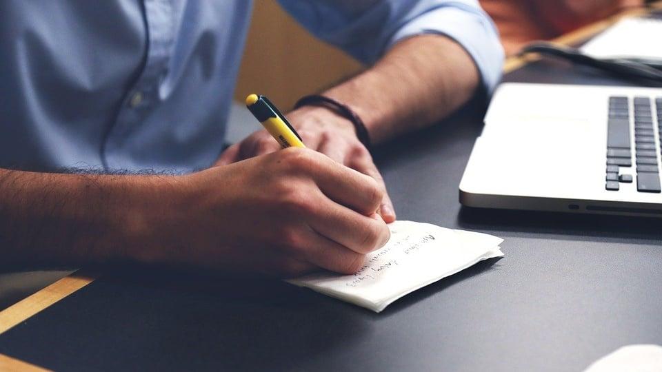 Concurso Câmara Passa Vinte - MG: homem escreve em pedaço de papel