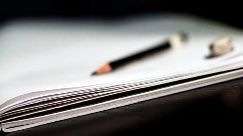 Concurso Campos Belos - GO: foto de um caderno com um lápis em cima