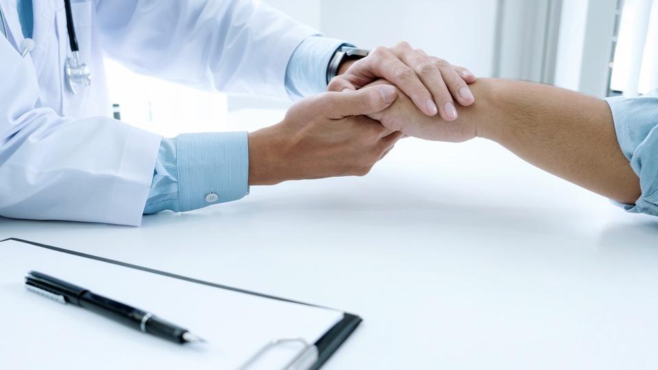 Concurso Centro Universitário de Adamantina - SP: profissional de saúde aperta mão de paciente; em primeiro plano está um prontuário médico e caneta por cima dele