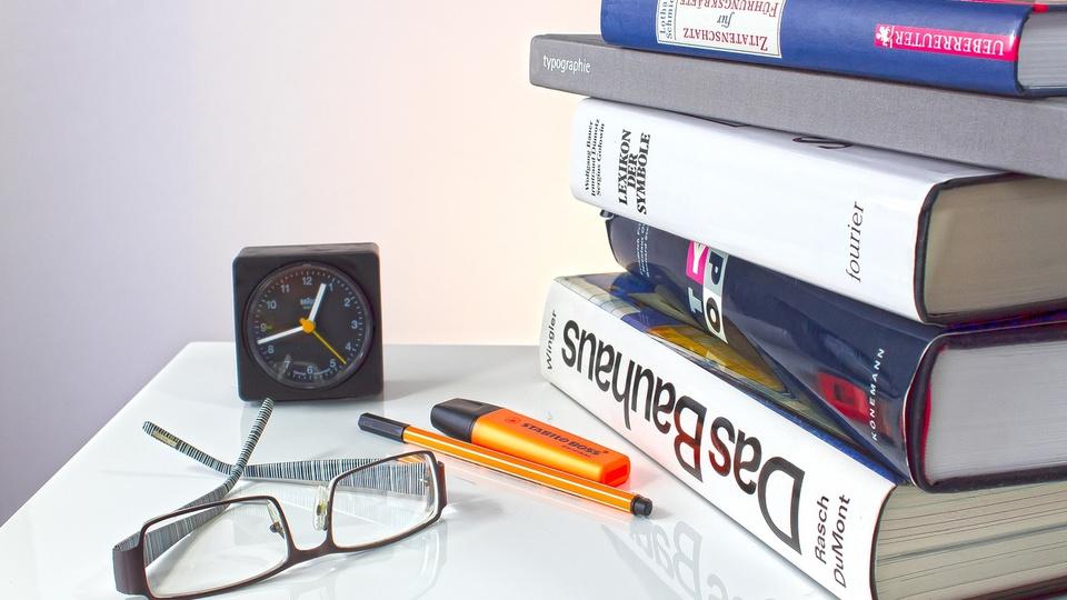 Concurso Prefeitura de Cezarina: livros empilhados, relógio de mesa, lápis e óculos em cima de superfície