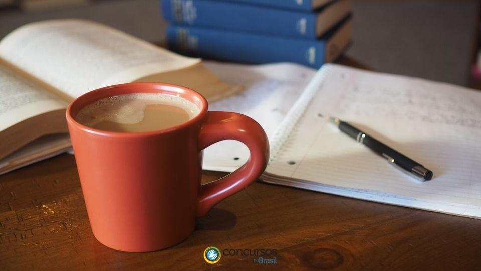 concurso contagem mg: a foto mostra xícara vermelha de café com leite, caneta, caderno e livros
