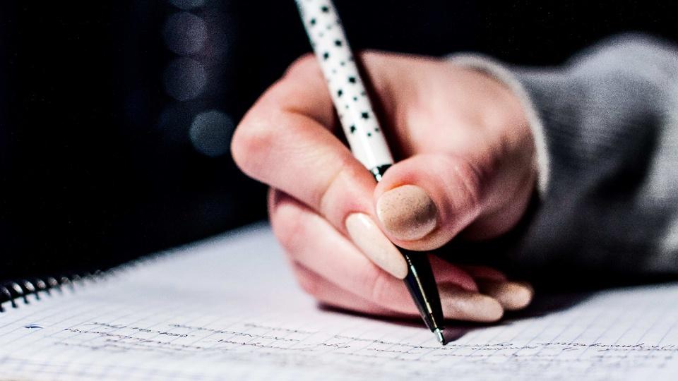 Concurso CONTER DF: enquadramento fechado em mão escrevendo em caderno