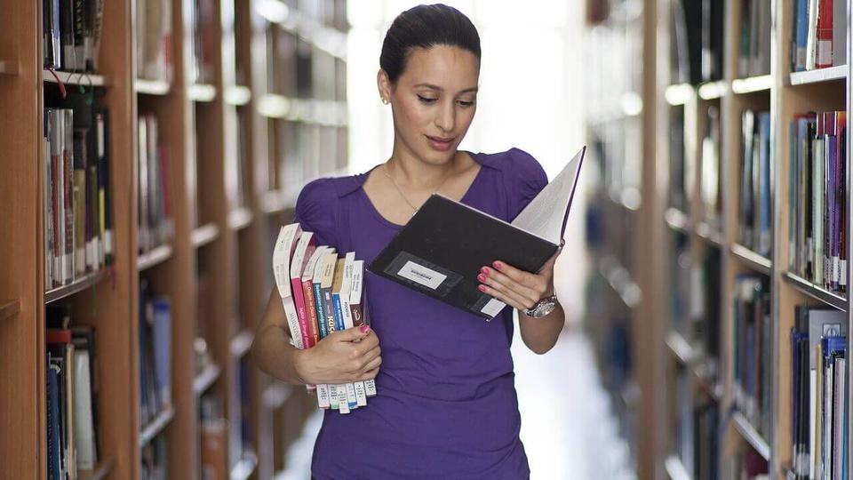 concurso crb 14ª Região: a imagem mostra mulher segurando livros em corredor de biblioteca entre estantes de livros
