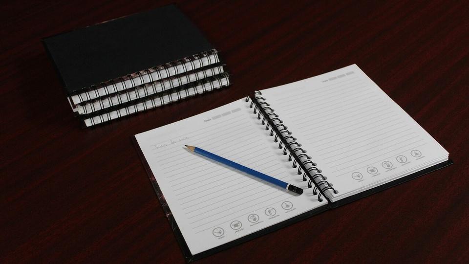 concurso CRECI RJ: a imagem mostra uma pilha de caderninhos pretos e um caderno aberto com caneta sobre a mesa