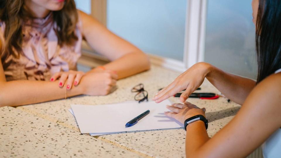 CREDEQ GO: a foto mostra mulheres conversando; papel, lápis e óculos sobre uma mesa