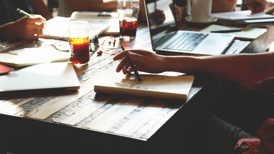 Concurso CREFITO 4 MG, pessoa sentada em uma mesa com caneta na mão