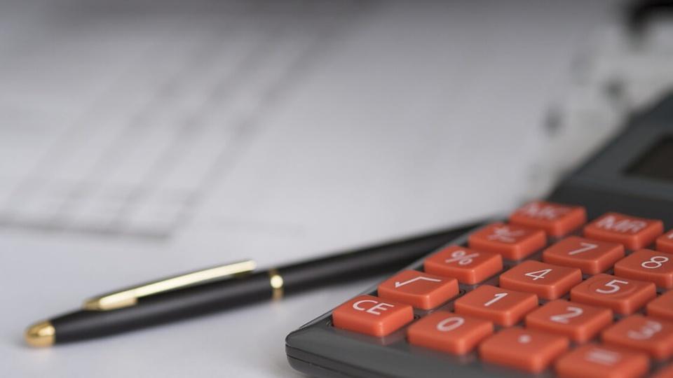 Concurso CRM MG: #PraCegoVer calculadora com teclas vermelhas ao lado de caneta na cor preta