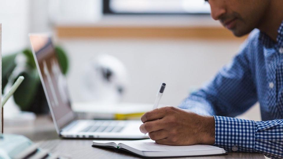 Concurso CRP MG: homem vestido de camisa xadrez escrevendo em caderno ao lado de notebook aberto