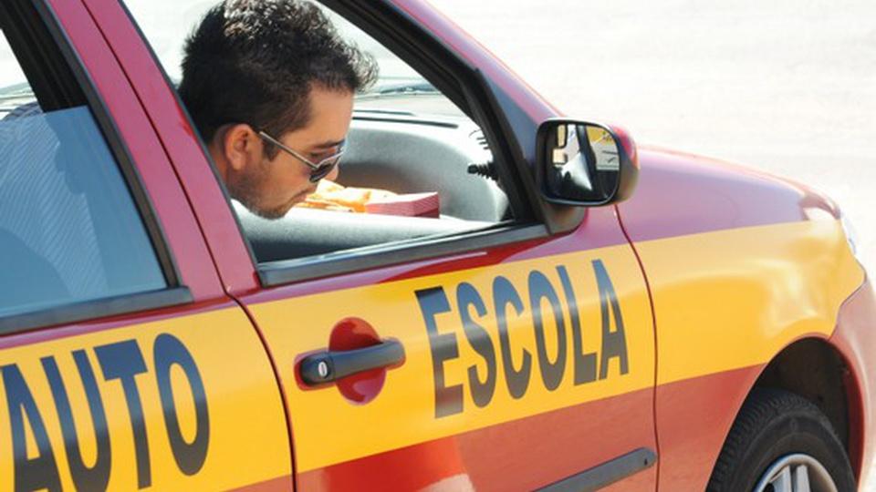 Concurso DETRAN PI: carro de auto-escola. Uma pessoa está olhando para fora da janela
