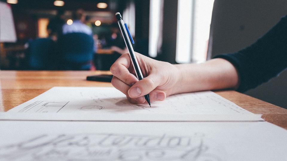 Concurso DETRAN - RN: foco em mão escrevendo em folha de papel com caneta