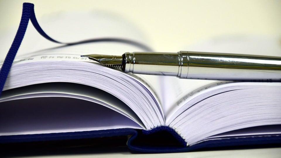 Concurso DPDF: a imagem mostra agenda aberta com caneta em cima