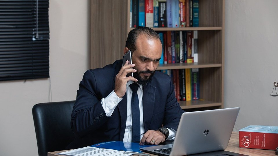 Concurso DPE CE: homem de terno e gravata, sentado, falando ao telefone e olhando para tela de notebook