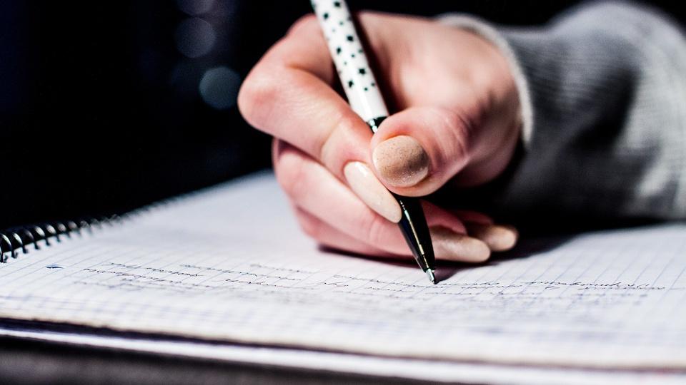Concurso e processo seletivo Prefeitura de Prados - MG, pessoa escrevendo em um caderno