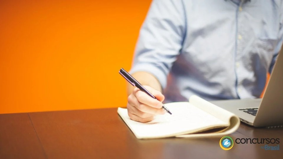 Concurso Embasa: a foto mostra um homem fazendo anotações no caderno e utilizando o notebook