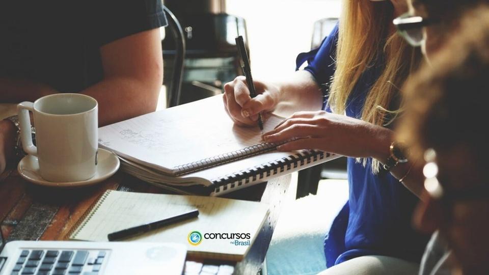 Concurso FESAUDE NITERÓI: mulher de blusa azul escrevendo em um caderno.