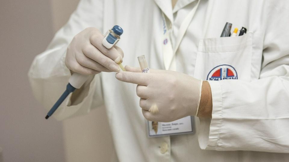 Concurso FESF-SUS BA: a foto mostra um profissional da saúde com luvas, jaleco e aparelho laboratorial