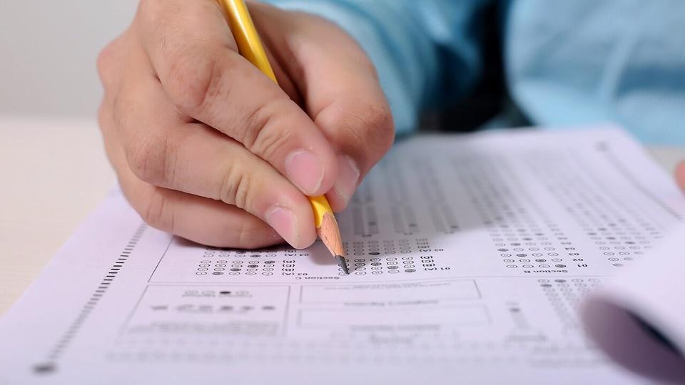 Concurso FSNH: pessoa segurando um lápis amarelo e preenchendo um formulário