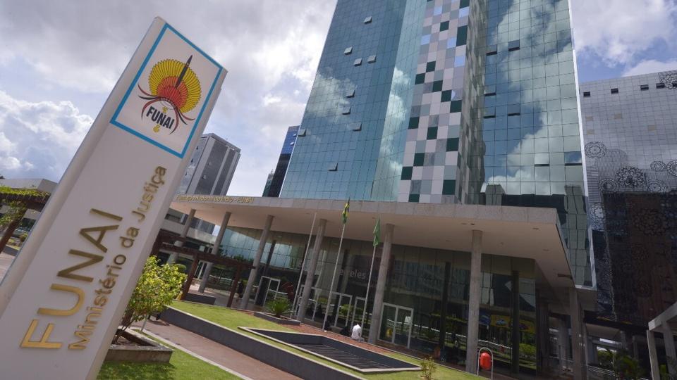 Concurso FUNAI: #PraCegoVer fachada da sede da FUNAI, com prédio de estrutura espelhada. Destaque vai para o letreiro da FUNAI, que está logo na frente do prédio