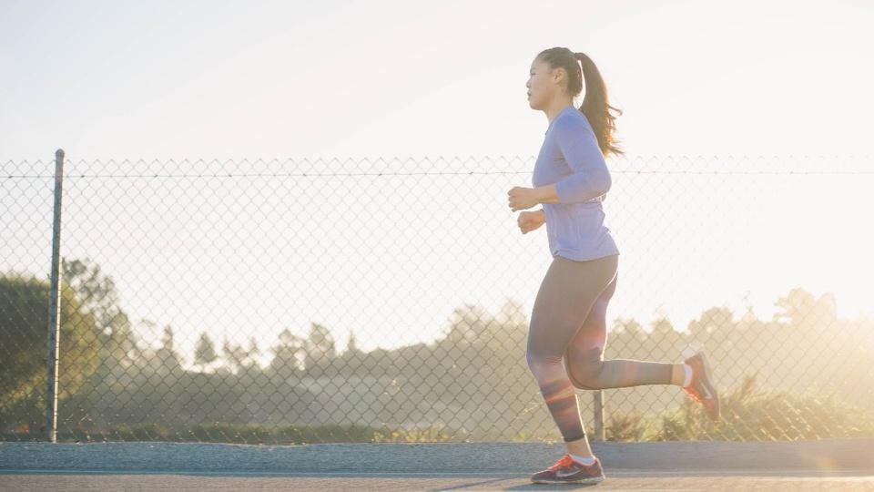 concurso FUNCEL: mulher correndo. Ela está com vestimentas feitas para exercícios físicos. Destaque também para a paisagem de fundo