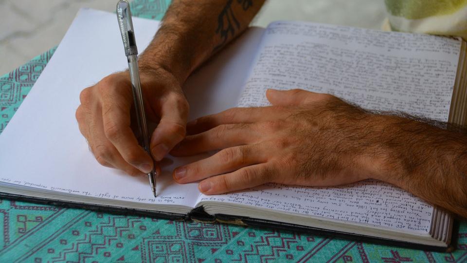 Concurso IGE: pessoa escrevendo em caderno