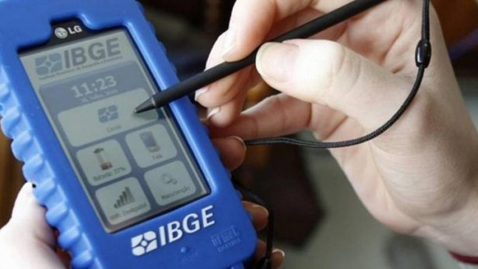 concurso ibge: a imagem mostra mão segurando aparelho do IBGE com questionário