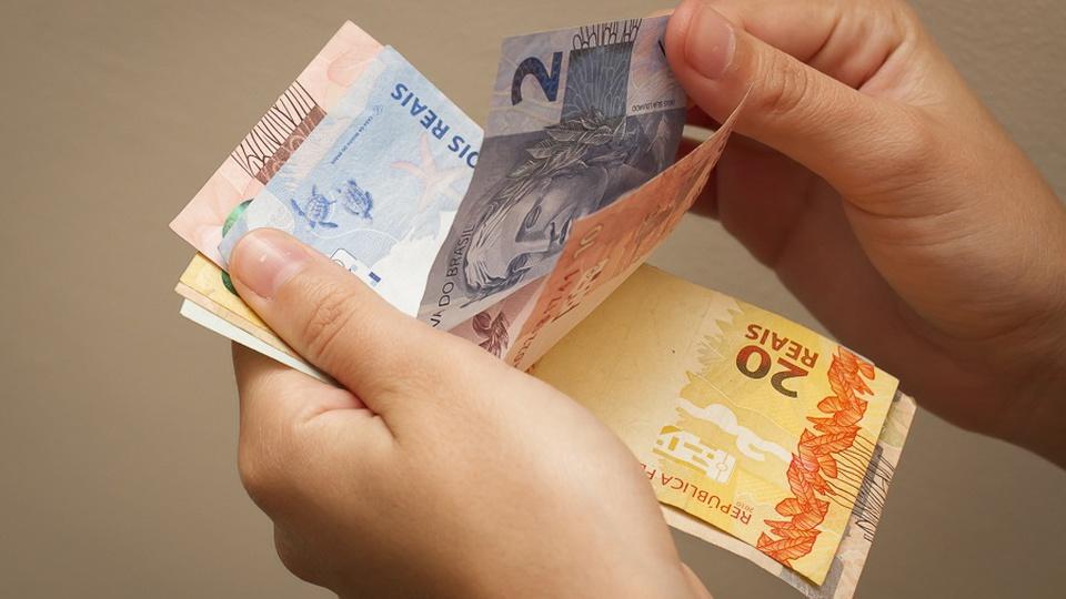 Concurso IBGE: mãos de uma pessoa contando notas de dinheiro