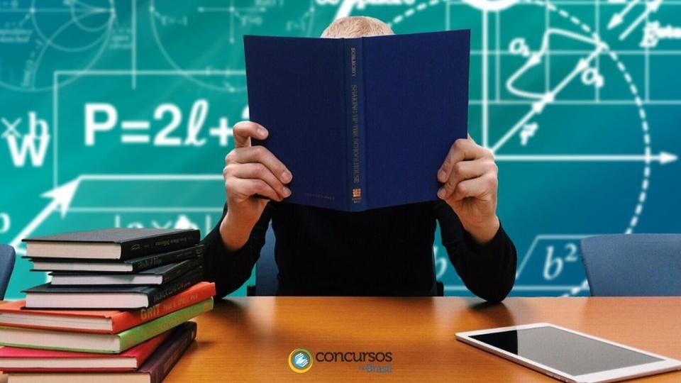 concurso câmara de luiziana PR: a foto mostra um home segurando um livro de capa azul, sentado em frente ao quadro escolar